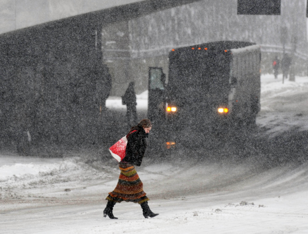 Marianne Stewart of Albany crosses a road as snow falls on Thursday in Albany, N.Y. The National Weather Service said some areas from Buffalo to Albany could get a total of up to 14 inches by the time the coastal storm moved out Friday morning.