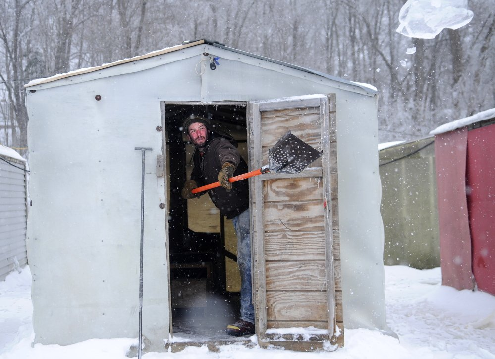 Mike Abbott tosses ice out of a smelt shack on Thursday at Baker's Smelt Camps in Pittston. Abbott cleaned the ice out of race holes at the camps on the Kennebec River before anglers arrived to fish an afternoon tide.