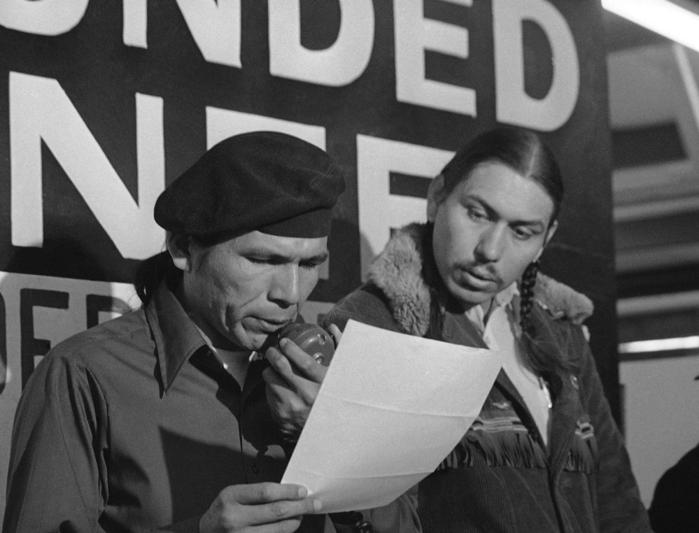 American Indian Movement leader Dennis Banks, left, reads a government offer seeking an end to the takeover of Wounded Knee, S.D., in 1973. Looking on is AIM leader Carter Camp.