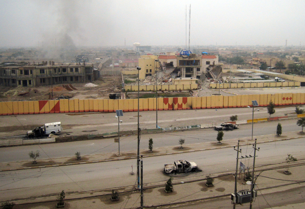 Burned vehicles litter an empty street, and buildings, including a provincial government building, center in the background, show damage in Fallujah, 40 miles west of Baghdad, Iraq, on Friday.