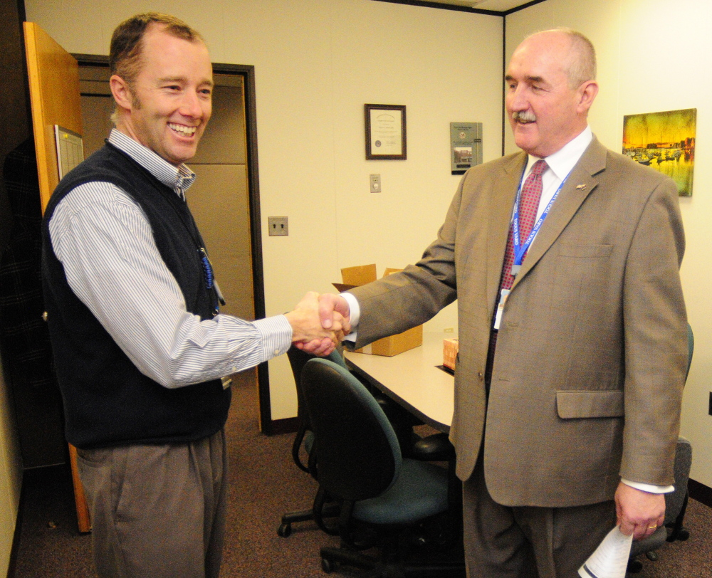 Ryan Lilly, director of the VA Maine Healthcare Systems-Togus, left, congratulates Scott Karczewski, the retiring director of the Togus regional office, on Friday.