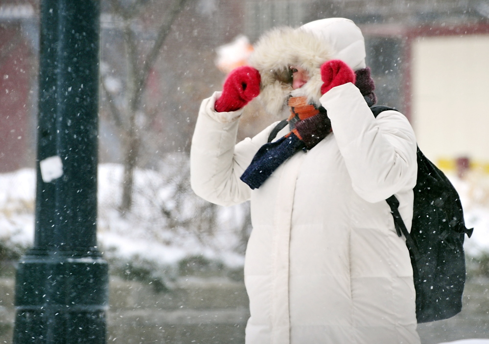 A pedestrian is dressed for the weather as she heads down Forest Avenue in Portland as snow blows on Friday.