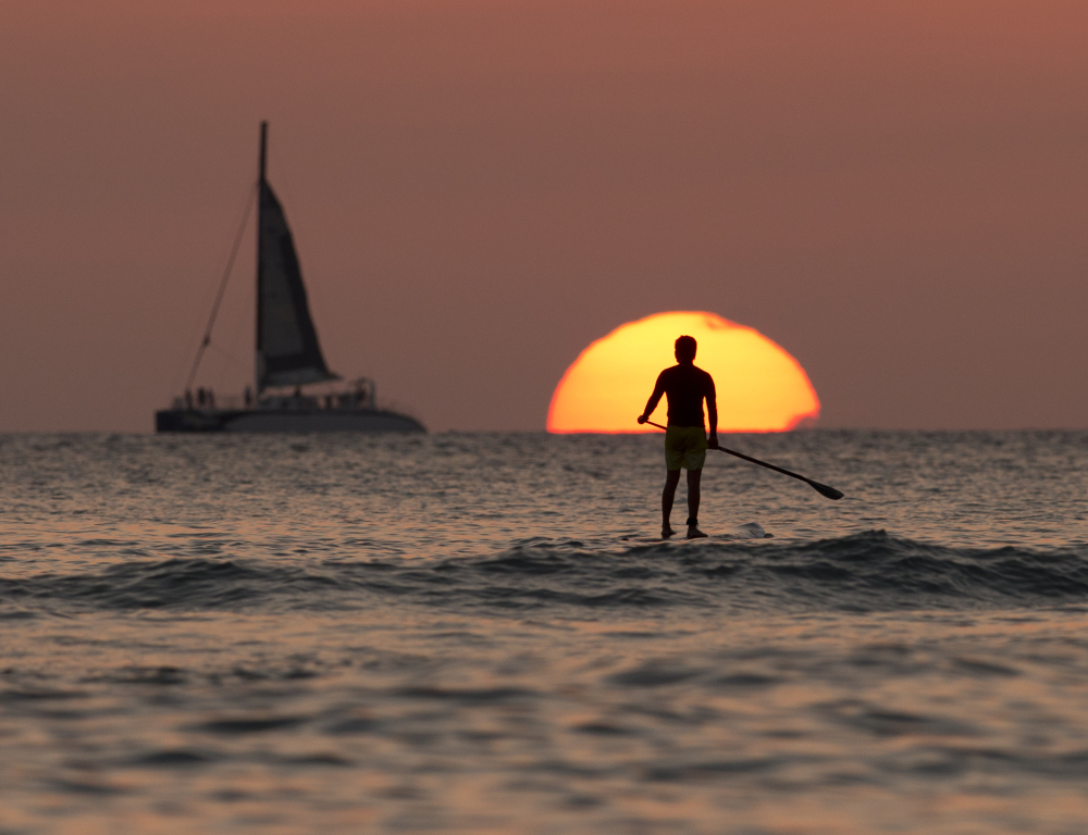 A paddle boarder plies waters off Waikiki Beach. Hawaii has acted progressively on the environment, a stance that puts off new business, one of its rare Republican leaders says.
