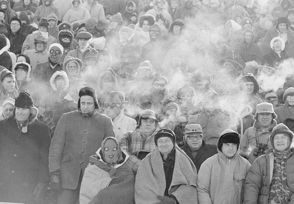 In this Dec. 31, 1967 file photo, fans watch the Green Bay Packers play the Dallas Cowboys in the NFL Championship game in Green Bay, Wisc. Comparisons to the legendary 1967 Ice Bowl are inevitable when the mercury dips below zero at Lambeau Field. But even if temperatures sink to minus-13 Sunday at the 49ers-Packers playoff game, modern technology will ensure fans are warmer than their predecessors.