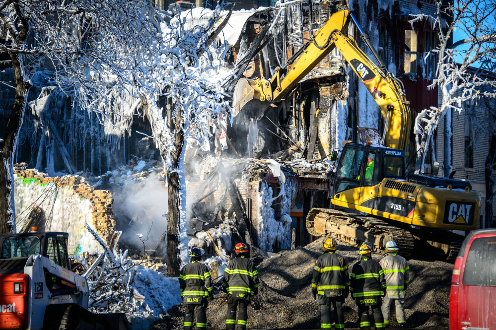 Investigators search for victims from a deadly apartment fire in Minneapolis. (AP Photo/The Star Tribune, Glen Stubbe)
