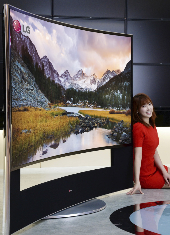A model poses with LG Electronics' 105-inch, ultra-HD TV with a curved screen in Seoul, South Korea. The curved screen is supposed to improve the viewing angle. Also showing off bigger, smarter TVs at this week's Consumer Electronics Show will be Samsung. One of its TVs is 9 feet wide.