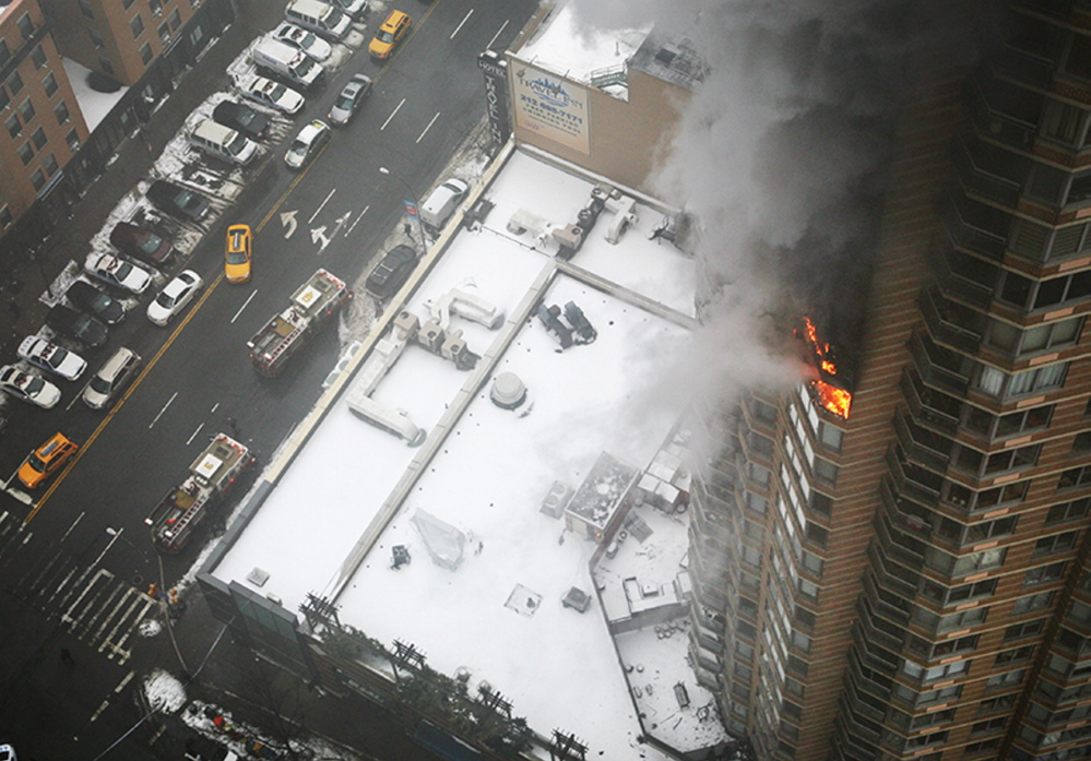 Flames and smoke emerge from the 20th floor of the Strand apartment building near Times Square, Sunday in New York. Authorities say two people have been critically injured in the three-alarm high-rise fire.