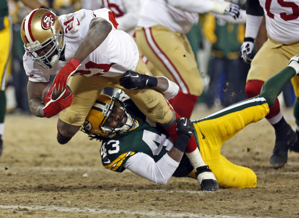 San Francisco running back Frank Gore runs through a tackle by Packers free safety M.D. Jennings to score a touchdown in the first half of their NFC wild-card game Sunday in Green Bay , Wis. The 49ers won, 23-20.
