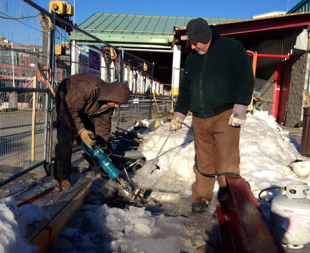 Brian Trafford, left, and Jason Thibeault, who work for Northeast Contractors, use a blow torch and a jackhammer to melt the ice and remove a metal plate during renovations of the Casco Bay Lines terminal.