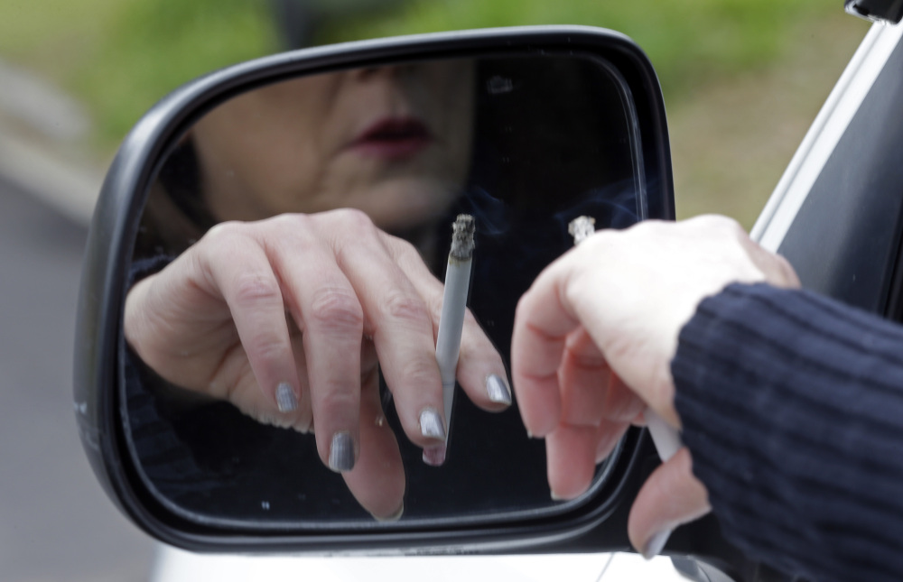 A woman smokes while sitting in her truck in Hayneville, Ala. Anti-smoking measures have saved roughly 8 million U.S. lives since a landmark 1964 report, a study estimates.