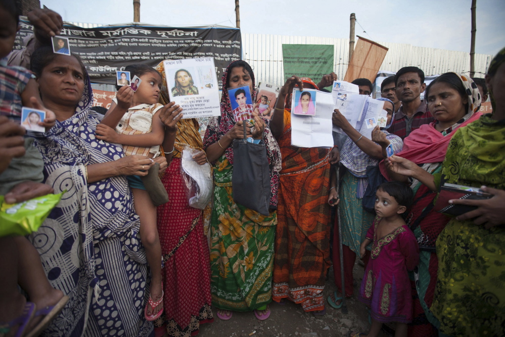 Relatives of the victims of the Rana Plaza factory disaster display photos of their loved ones at the site of the tragedy in Savar, Bangladesh, on Oct. 24, the six-month anniversary of the deadly building collapse. Because it includes enforcement mechanisms, a European-led initiative is a promising approach to helping improve worker safety in Bangladesh.