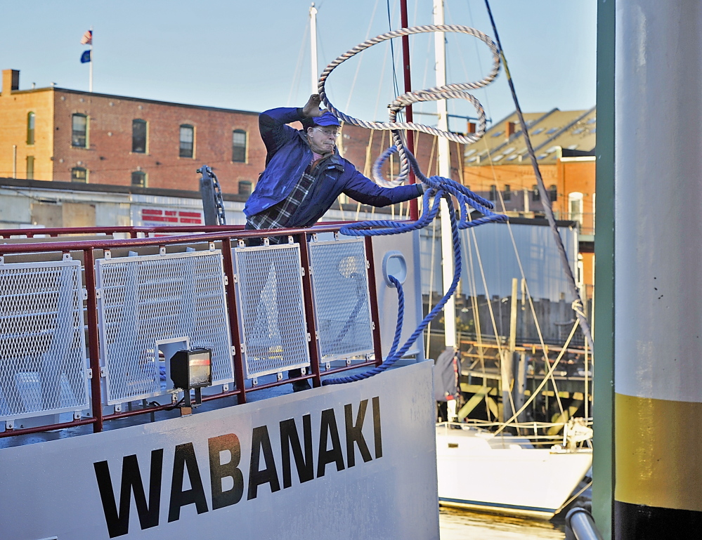 Dave Crowley, a Casco Bay Lines board member from Cliff Island, helps out with the docking as he throws a line from the Wabanaki to the bollard on the ferry terminal pier.