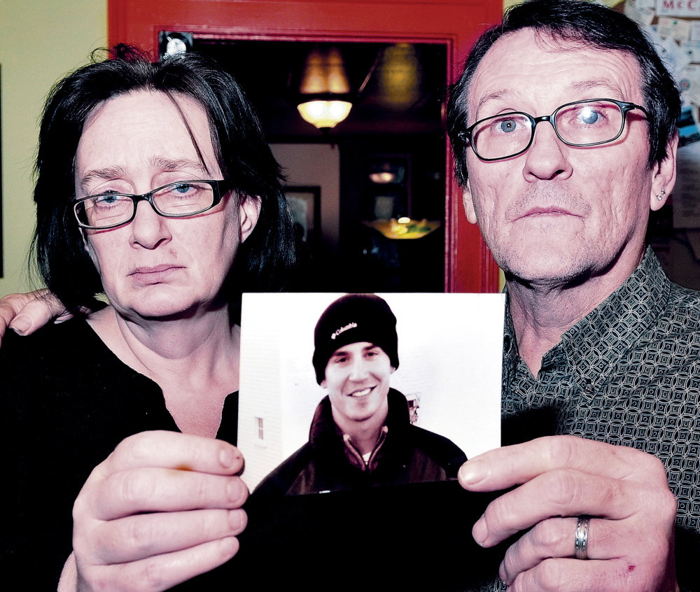 Lorna and Michael Smilek hold a 2006 photograph of Michael's son, Justin Crowley-Smilek, who was shot and killed after he confronted Farmington police in 2011.