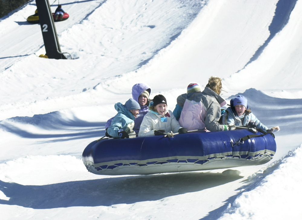A group of girls bombs down the slope at Oxford Plains Snow Tubing.