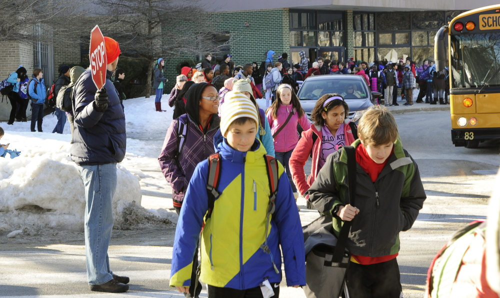 Crossing guide Adam Waxman, left, assists students leaving King Middle School in Portland on Wednesday.