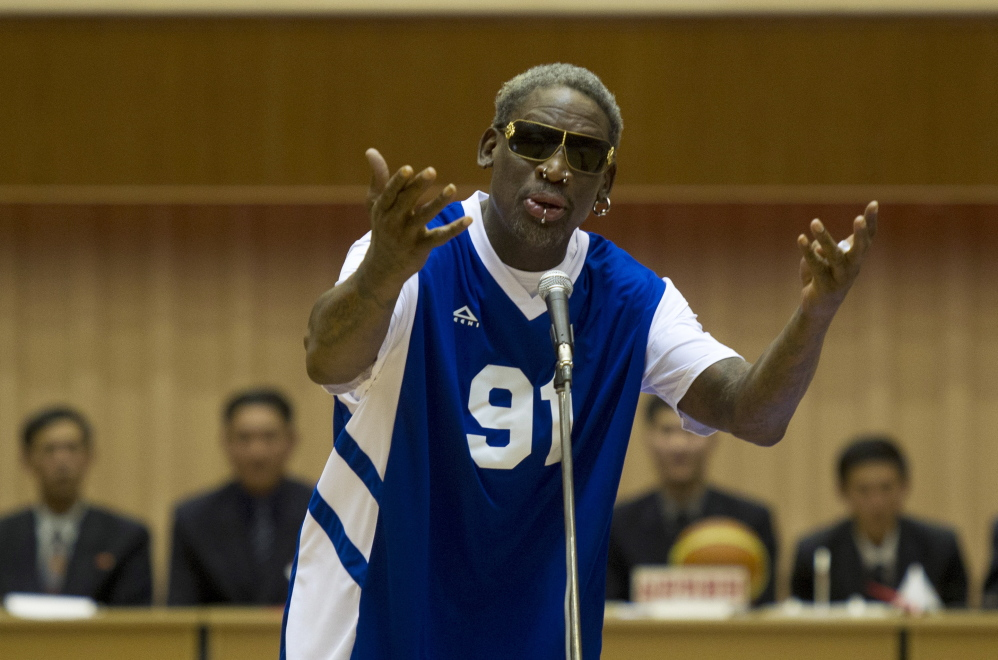 """Dennis Rodman sings """"Happy Birthday"""" to North Korean leader Kim Jong Un, seated above in the stands, before an exhibition basketball game at an indoor stadium in Pyongyang, North Korea on Wednesday."""