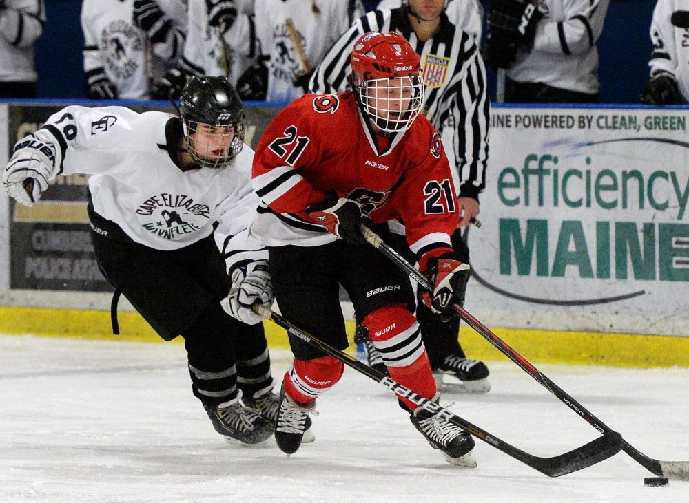 Sami Shoebottom of Scarborough takes the puck down the ice Wednesday as Kate Ginder of Cape Elizabeth/Waynflete moves in on defense. Shoebottom scored three goals and added an assist to help the undefeated Red Storm recover from a 2-0 deficit and come away with a 5-2 victory.