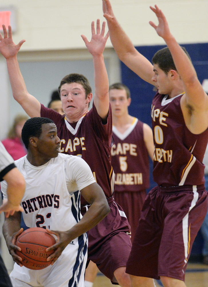 Sam Johnson of Gray-New Gloucester looks for an open teammate as Cape Elizabeth's Spencer Harriman, right, and Eddie Galvin defend. Cape Elizabeth won, 64-52.