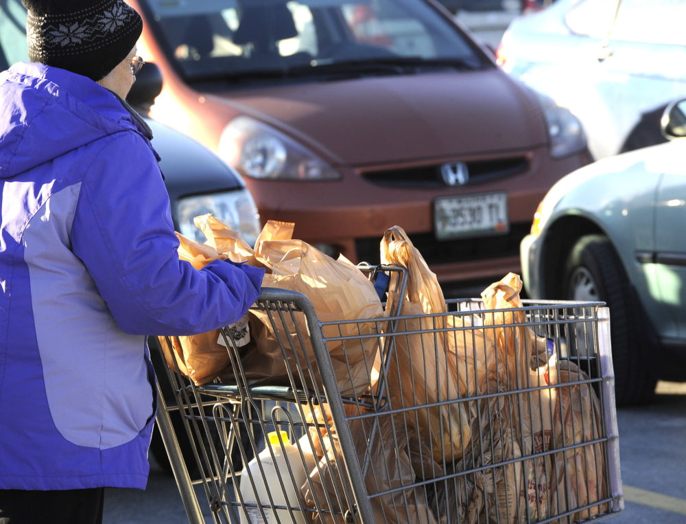 A shopper leaves Hannaford in Portland on Thursday with groceries in plastic bags.
