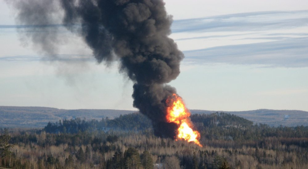 A large fireball rises from the site of a train derailment in New Brunswick, Canada, on Friday as officials used a controlled explosion to blast holes in three tanker cars in the hopes of fighting a large fire that continues to burn two and half days after the incident.
