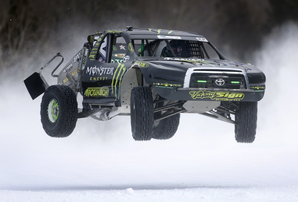 Above, Johnny Greaves of Green Bay, Wis., flies across the finish line while racing in the Red Bull Frozen Rush short-course off-road truck race Friday at the Sunday River ski area in Newry. At right, Carl Renezeder of Laguna Beach, Calif., sails over a jump.