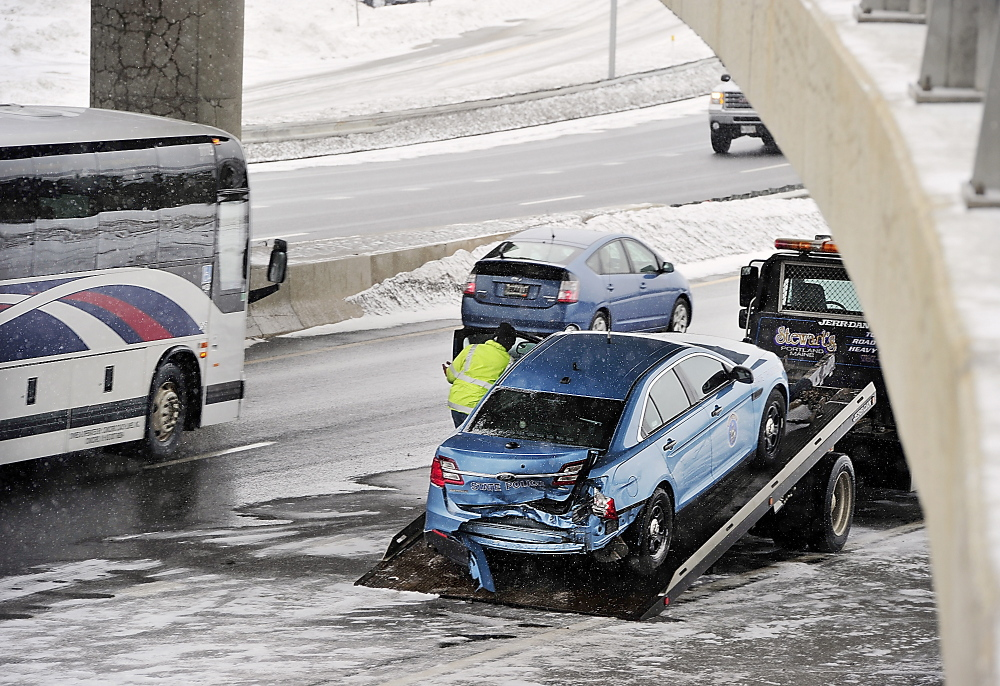 A tow truck driver for Stewart's towing company prepares a Maine State Police trooper's car for towing under the Washington Avenue exit overpass on Interstate 295 on Friday. The car was rear-ended in a multi-car accident blamed on black ice and snow.