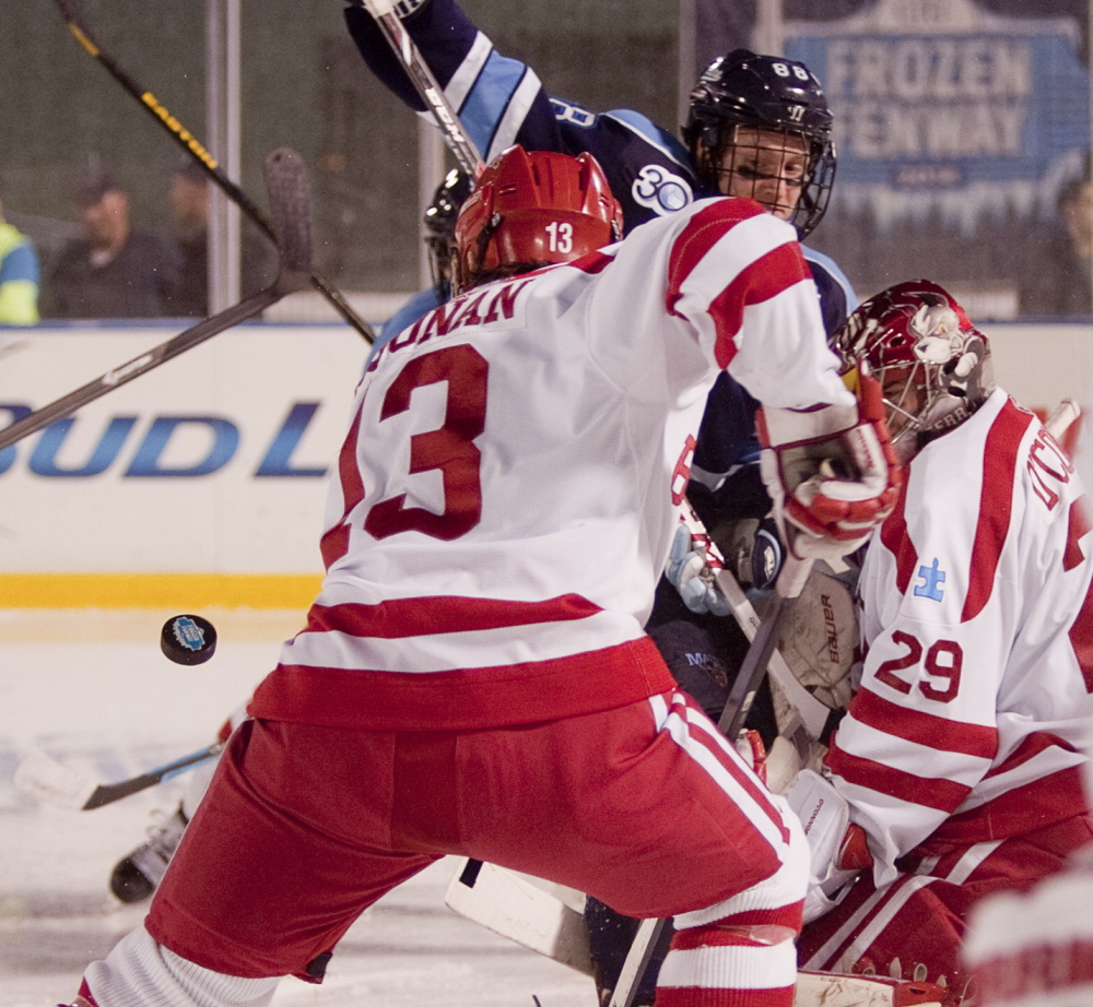 Boston University goalie Matt O'Conner, right, saw plenty of action and allowed four first-period goals, forcing the Terriers to make a change. Maine went on to win 7-3.