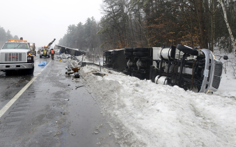 A tractor trailer lies on the side of the Maine Turnpike near exit 55 in Falmouth Saturday after being involved in a multivehicle accident.