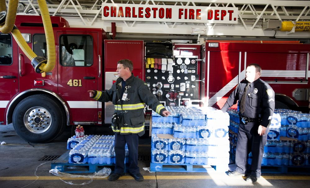 Police officers and firefighters hand out cases of water to those in need at the Charleston Fire Department Station One in Charleston, W.Va., on Saturday. About 5,000 gallons of a chemical used in the coal cleaning process leaked into the Elk River, forcing officials to restrict water use in nine counties.
