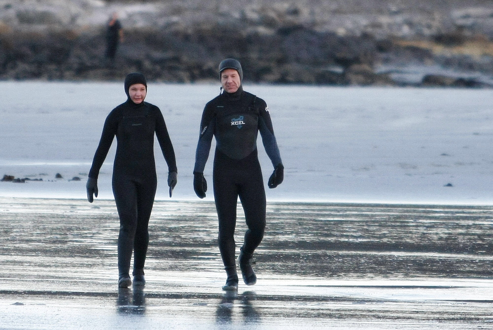 Two surfers walk along Goose Rocks Beach in Kennebunkport after being found Sunday on Timber Island. The two were separated from a third surfer who came to shore to get help.