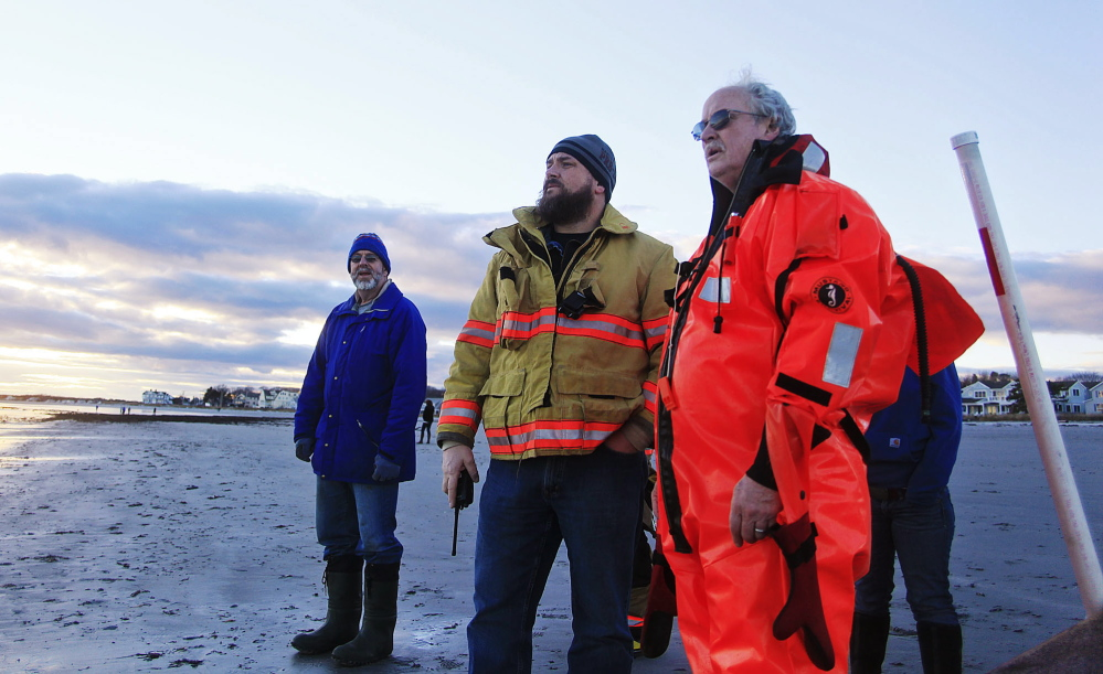 Kennebunkport Fire Department Capt. Mike McGrath, far right, and other emergency personnel watch for two missing surfers at Goose Rocks Beach in Kennebunkport on Sunday.