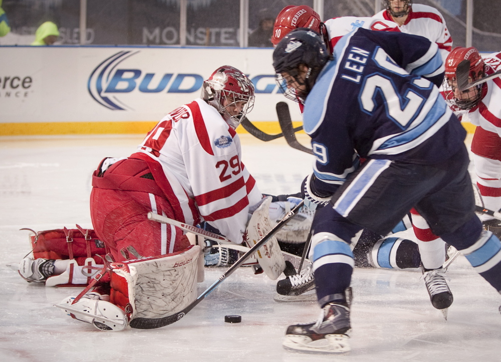 "University of Maine player Connor Leen pressures Boston University goalie Matt O'Connor during the ""Frozen Fenway"" outdoor hockey game played despite rain and lightning on Saturday."