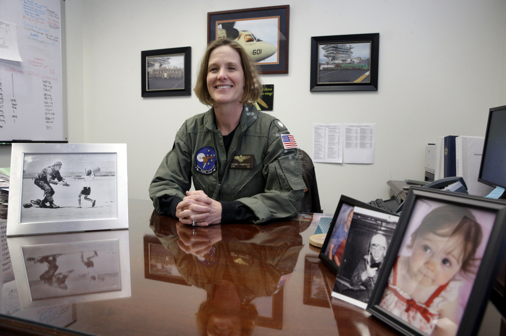 U.S. Navy Cmdr. Valerie Overstreet poses Thursday at her desk decorated with family photos, on the U.S. Naval Academy campus in Annapolis, Md.