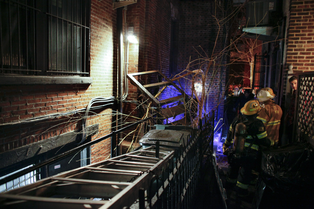 Firefighters gather in an alley after a fire escape landing collapsed in the Rittenhouse Square section of Philadelphia early Sunday morning.