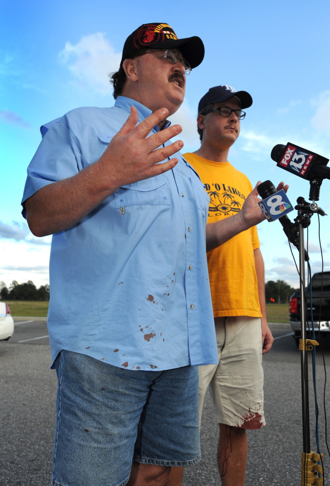 Charles Cummings, left, and Alex Cummings talk to the media after witnessing a shooting inside movie theater Monday in Wesley Chapel, Fla.