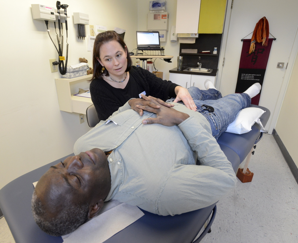 Dr. Magili Quinn examines Frederick Kamegni at the Portland Community Health Center. Kamegni is applying for political asylum and may be eligible for health insurance under the new federal law.