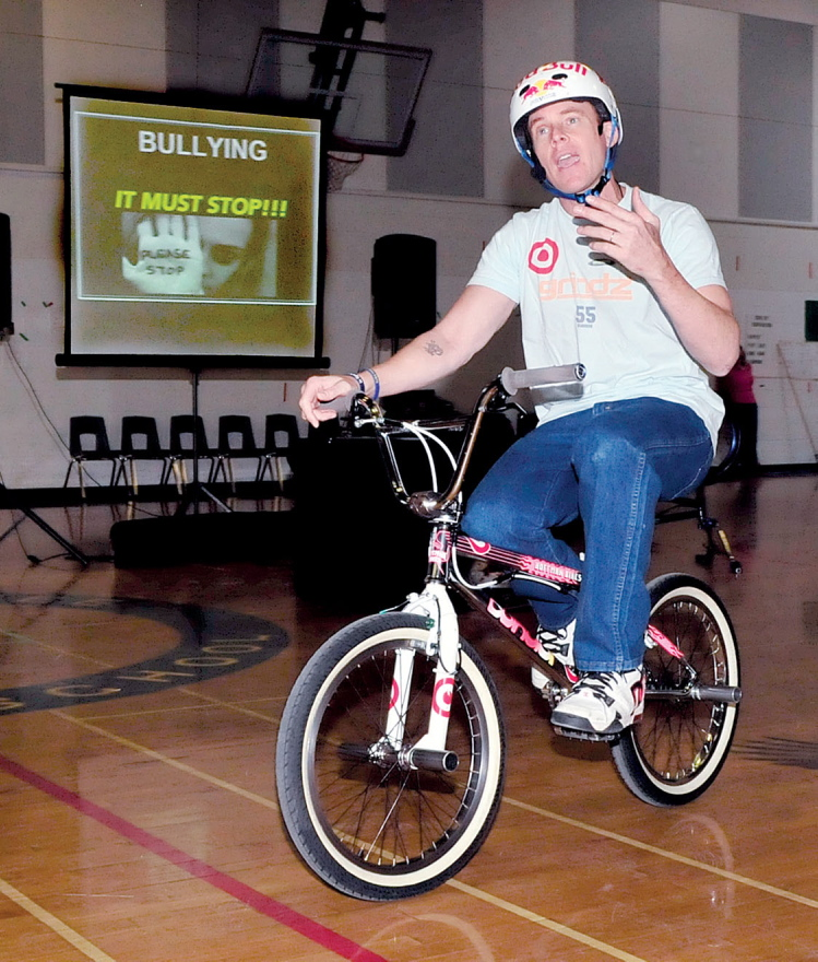 BULLY MESSAGE: Presenter Kevin Robinson rode a bike while delivering his antibullying message to Messalonskee Middle School students in Oakland on Monday. Robinson is an X Games athlete.