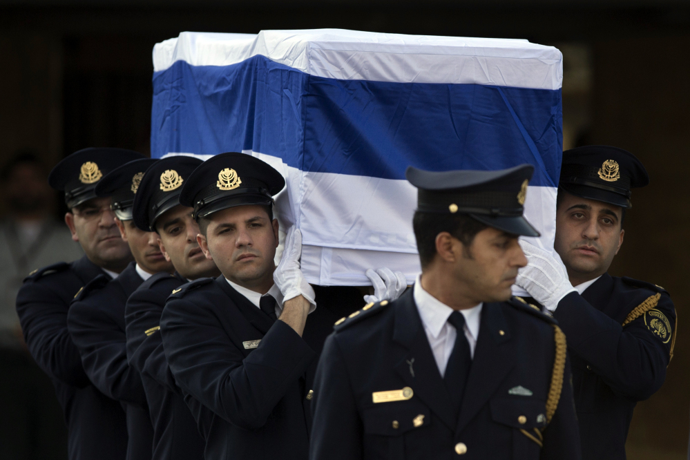 Members of the Knesset guard carry the coffin of late Israeli Prime Minister Ariel Sharon for the state memorial ceremony at the Knesset Plaza in Jerusalem on Monday.