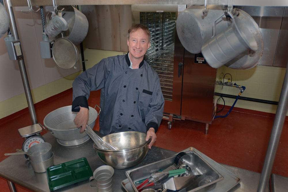 Ronald Adams, director of food services for Portland Public Schools, works in the district's new central kitchen, which allows the schools to process and store more food from Maine farms.