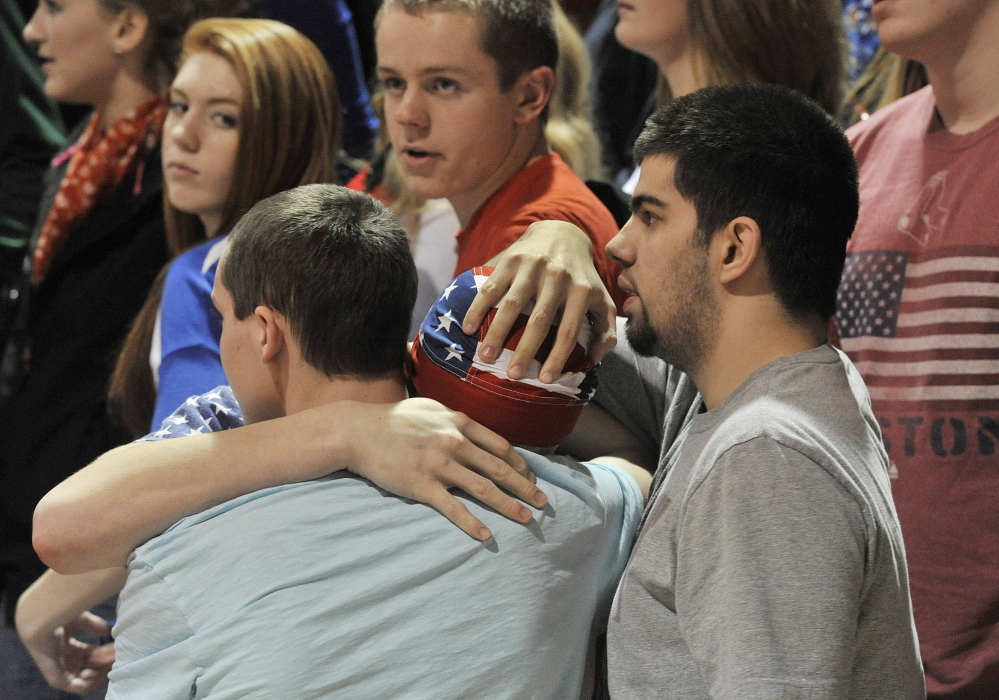 Dillon Reynolds (with flag bandanna) hugs Danie Petterson as Carl Cushman, right, provides support during a moment of silence in memory of his father and his father's girlfriend before the Bonny Eagle boys' basketball game against Portland at St. Joe's College on Tuesday.