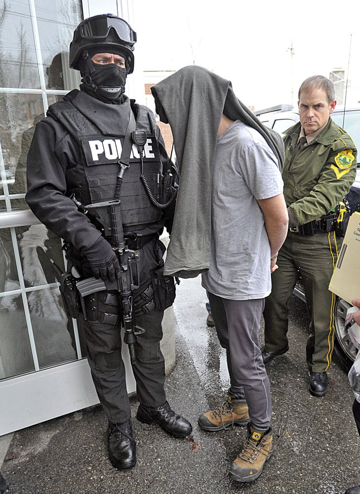 A suspect is taken into custody on Jan. 16, 2013, in Bennington, Vt., one of dozens of suspects rounded up in southwestern Vermont on charges related to the distribution and sale of illicit drugs.