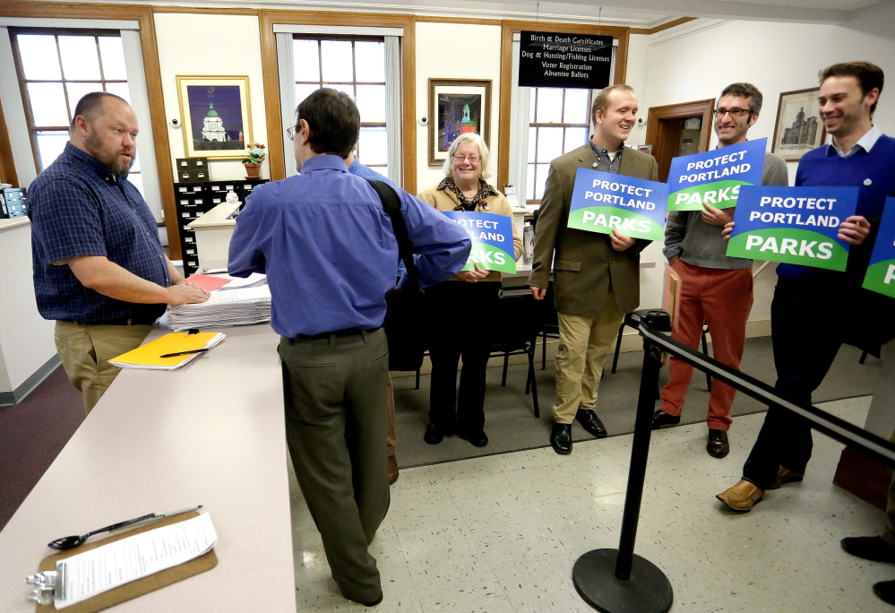 Portland election administrator Bud Philbrick accepts a stack of petitions from Robert Levin, attorney for Friends of Congress Square Park, in the clerk's office at Portland City Hall on Thursday.