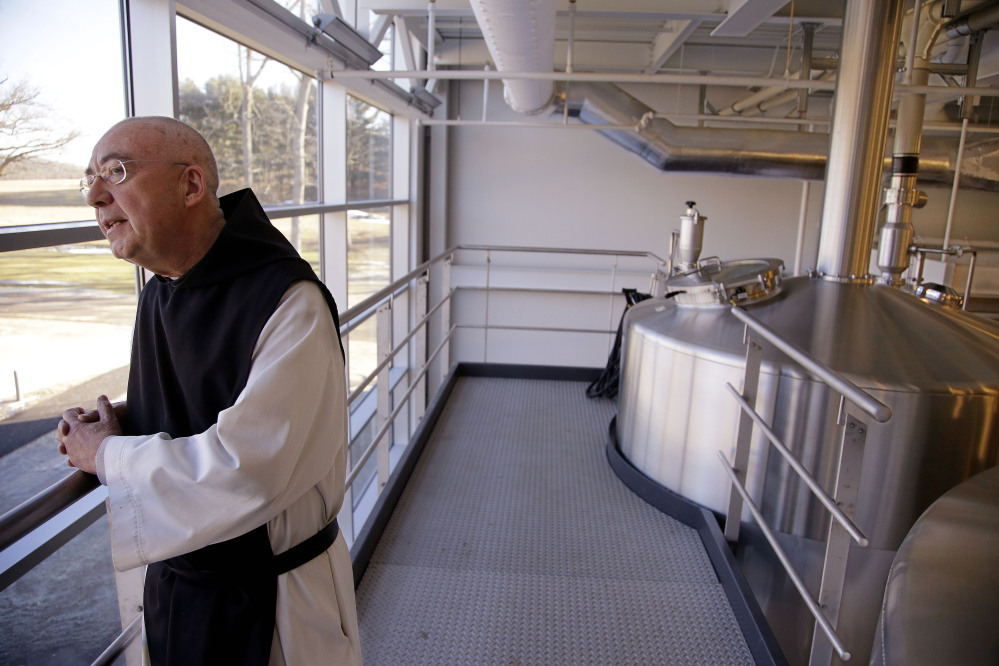 Spencer Brewery Director Father Isaac stands near the top of the facility's fermentation tanks and looks out a window onto the abbey's grounds in Spencer, Mass. Father Isaac was a potter before joining the Trappist community 35 years ago. He is one of 25 priests living in a community of 63 monks at St. Joseph's.
