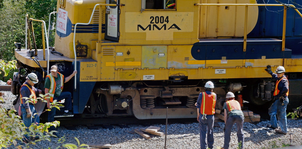 A Montreal, Maine & Atlantic Railway crew repairs tracks in Brownville last July. An unidentified company submitted an offer Thursday to purchase the bankrupt rail carrier. If enough qualified bids are received, the railroad will be sold at auction next Tuesday.