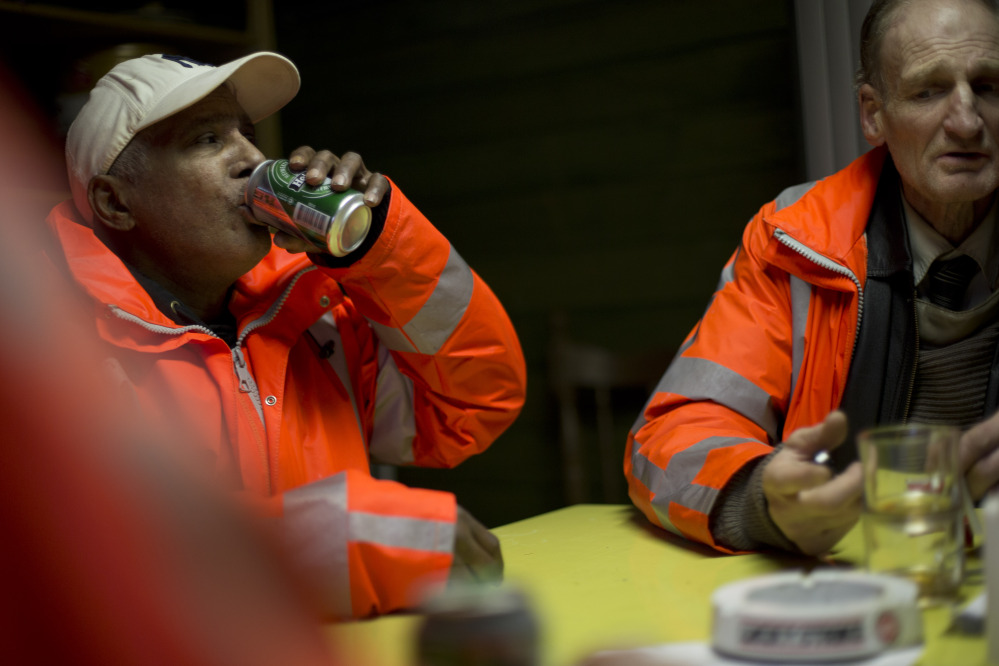 Ramon Mohamed Halim Smits, left, and Fred Schiphorst, participants in the pilot project, pause for a beer and cigarettes in their clubhouse in Amsterdam's eastern part Wednesday.