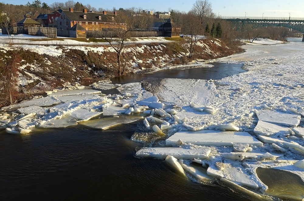 """Slabs of ice pile up on the Kennebec River in downtown Augusta on Friday. Once the ice is broken up, the pieces can move around. """"And if it refreezes, you end up with a big mass of ice,"""" said meteorologist Margaret Curtis."""