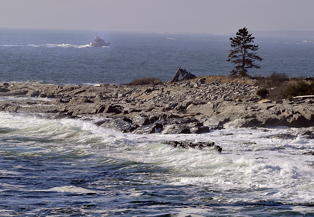 A boat cruises by Kresge Point near Pemaquid Point, where searchers looked for survivors of a reported sailboat sinking Friday.