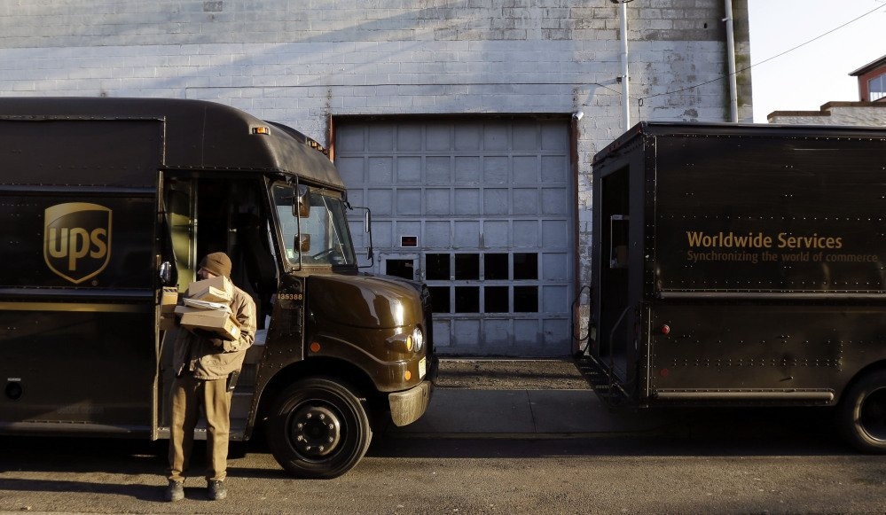 A UPS delivery worker moves packages in Newark, N.J. UPS says the rough holiday shipping season means its fourth-quarter profit will be smaller than expected.