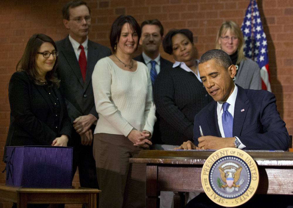 President Barack Obama signs the $1.1 trillion spending bill that funds the federal government through the end of September, in Washington on Friday.