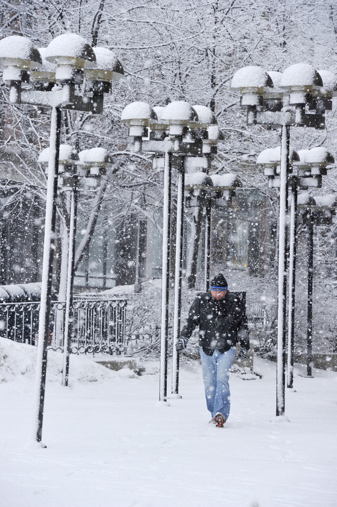 A man walks in Monument Square in Portland as snow falls Saturday. Greater Portland got 4 to 7 inches, with the highest amounts mainly along the coast and in York County.